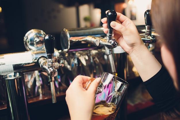 Equipaggia la pinta di birra versando a mano dietro il bancone.