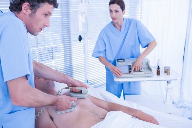 Equipe medica che rianima un uomo con un defibrillatore