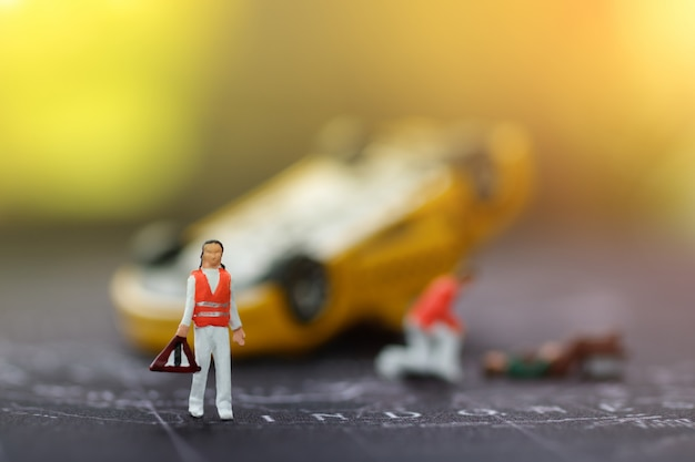 Equipe medica di emergenza in miniatura per aiutare le persone in incidenti stradali.