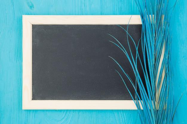 Erba azzurra dipinta vicino alla lavagna