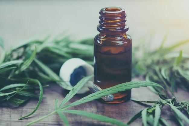 Erba di cannabis e foglie con estratti di olio in barattoli.