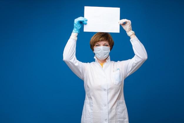 Erba medica femminile nella maschera facciale per protezione dall'epidemia del virus che tiene una carta