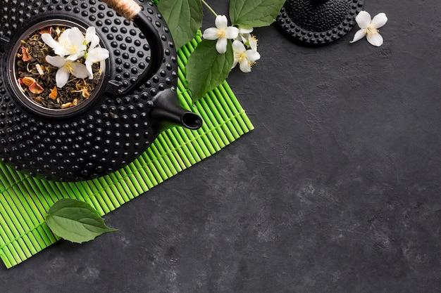 Erba secca del tè e fiore bianco del gelsomino su fondo nero