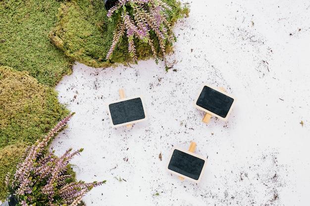 Erba sintetica e cartello bianco su sfondo bianco