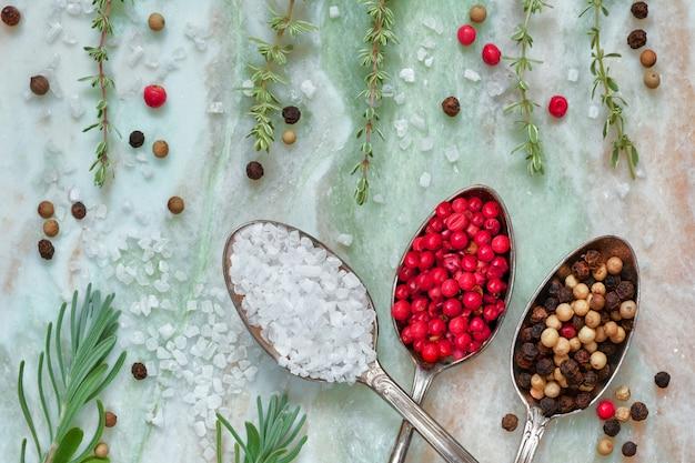 Erbe aromatiche con sale e pepe in cucchiai su pietra di marmo vista dall'alto, piatto disteso