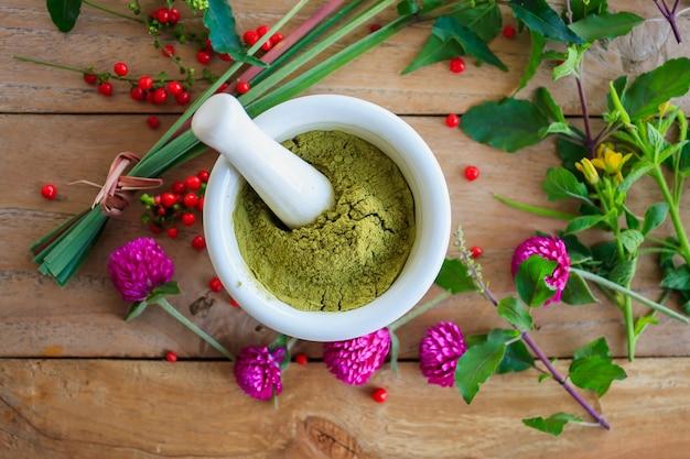 Erbe aromatiche fresche in polvere nel mortaio sul tavolo di legno, medicina alternativa