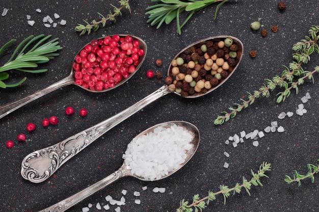 Erbe con sale e pepe in cucchiai su sfondo nero pietra ardesia