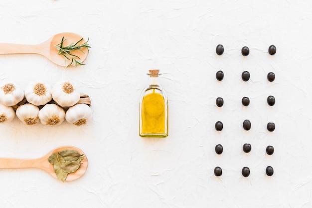 Erbe con un mazzo di bulbo di aglio e una bottiglia di olio