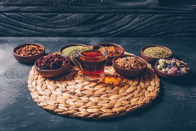 Erbe del tè di vista dell'angolo alto in ciotole con una tazza di tè su fondo strutturato di legno e scuro. orizzontale