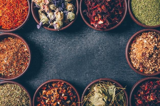 Erbe di tè vista dall'alto in ciotole su sfondo scuro con texture. spazio orizzontale per il testo