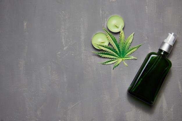 Erbe e foglie di cannabis per trattamento, brodo, tintura, estratto, olio. bottiglia con olio, candele