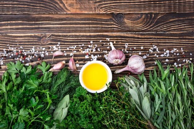 Erbe e spezie fresche, aglio, olio d'oliva su vecchio fondo di legno