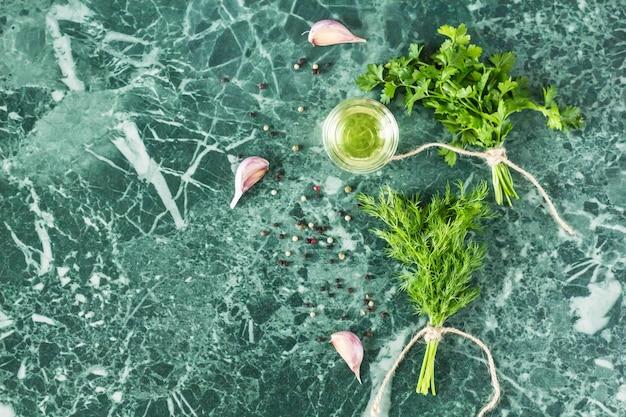 Erbe e spezie sulla vista del piano d'appoggio della pietra di marmo. prezzemolo, aneto, aglio, olio d'oliva e pepe
