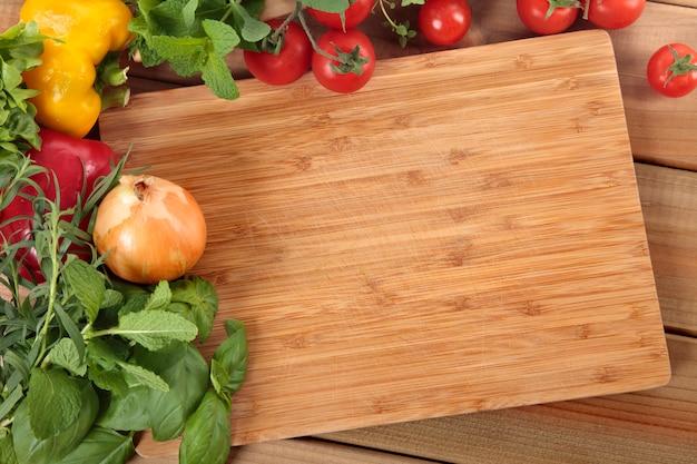 Erbe e verdure con un tagliere