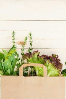 Erbe fresche in sacchetto di carta eco sulla tavola di legno. consegna del cibo.