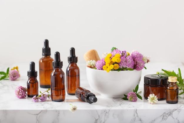 Erbe mediche dei fiori in olii essenziali del mortaio in bottiglie. medicina alternativa. trifoglio millefoglie tanaceto rosebay
