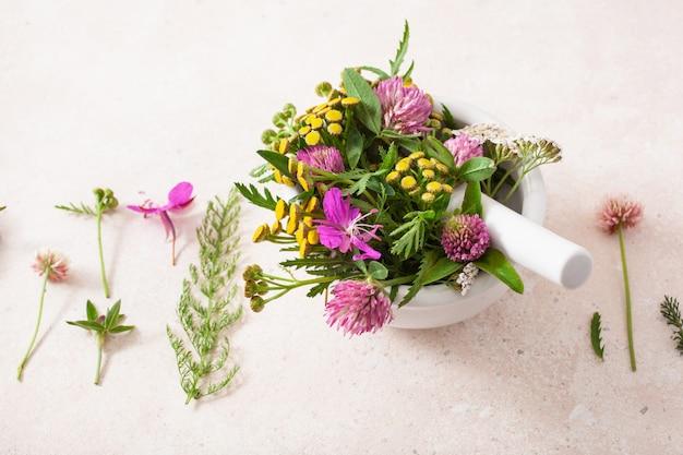 Erbe medicinali di fiori in mortaio. medicina alternativa. trifoglio millefoglie tanaceto rosebay