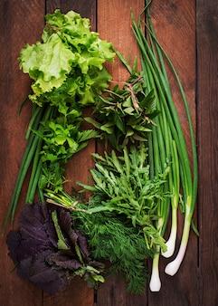 Erbe organiche fresche di varietà (lattuga, rucola, aneto, menta, lattuga rossa e cipolla) sulla tavola di legno in stile rustico. vista dall'alto