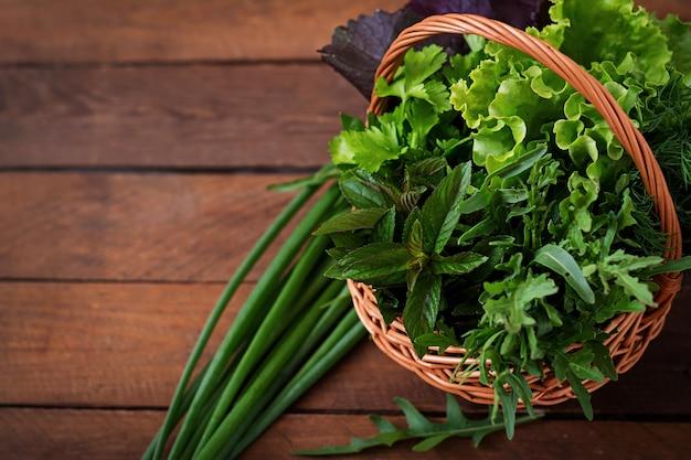 Erbe organiche fresche di varietà (lattuga, rucola, aneto, menta, lattuga rossa e cipolla) sulla tavola di legno in stile rustico.