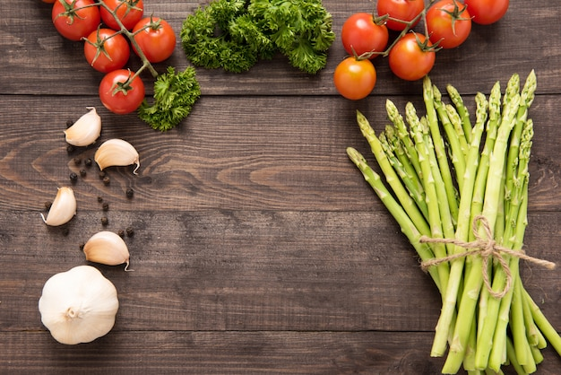 Erbe, pomodori e asparagi freschi su fondo di legno