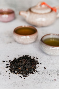 Erbe secche con tazze da tè su sfondo concreto
