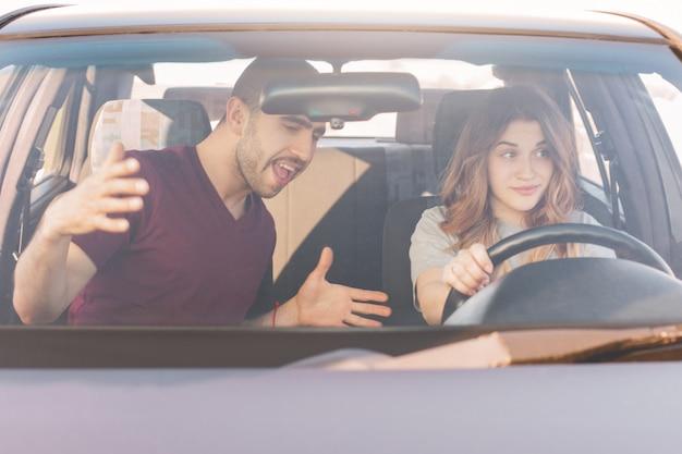 Esame di guida. l'istruttore maschio insegna all'auto femminile inesperta dell'azionamento dell'apprendista
