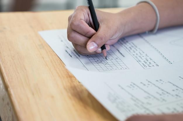 Esame di scrittura della matita della tenuta dello studente universitario della high school sul foglio di risposta di carta