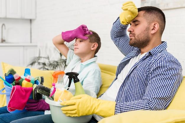 Esausto padre e figlio appoggiato sul divano