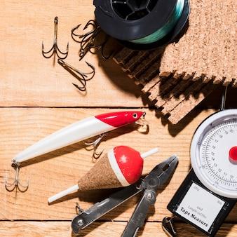 Esca per pescare; galleggiante; gancio con pinza e mulinello da pesca su scala di misurazione sopra la scrivania