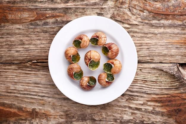 Escargots de bourgogne - lumache con burro alle erbe su fondo in legno