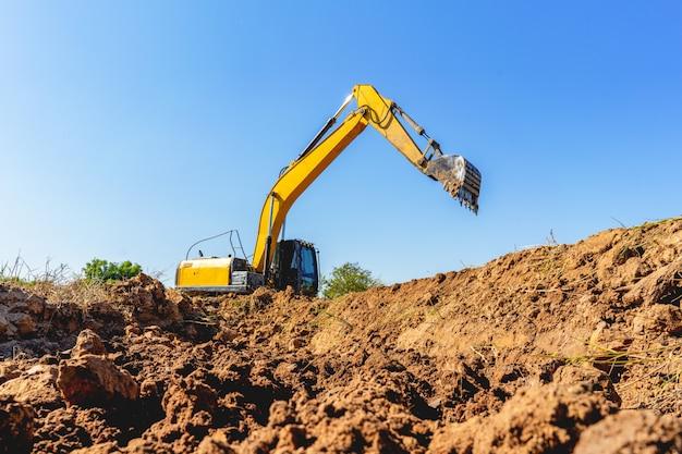 Escavatore a cucchiaia rovescia che scava il suolo un giorno soleggiato