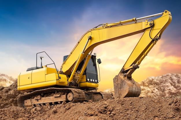 Escavatore a cucchiaia rovescia dell'escavatore sulla terra al cantiere nel fondo del tramonto