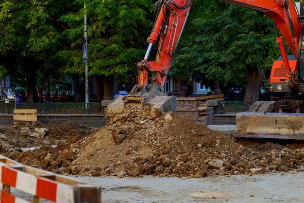 Escavatore che è parcheggiato ad una costruzione della strada principale