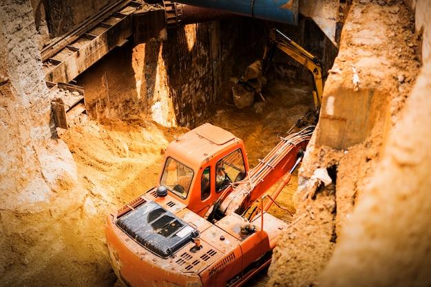 Escavatore che lavora con terreno rosso e polveroso
