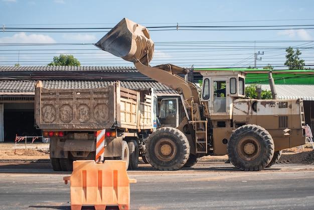 Escavatore cingolato del lavoratore sull'asfalto della via per la riparazione della strada