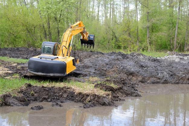 Escavatore con il braccio lungo in palude che scava il canale del fiume in campagna