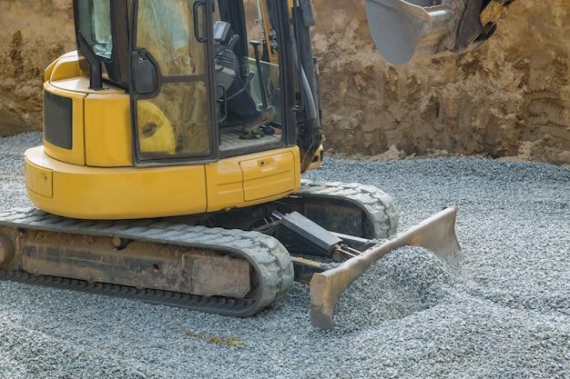 Escavatore con un secchio abbassato pietre di ghiaia per la costruzione di fondamenta