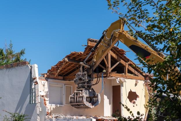Escavatore da cantiere giallo demolendo casa per la ricostruzione