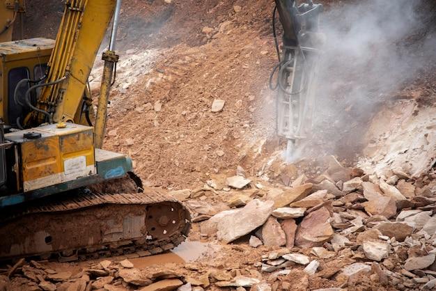 Escavatore di perforazione in cima alle rocce al cantiere di infrastrutture di fondazione