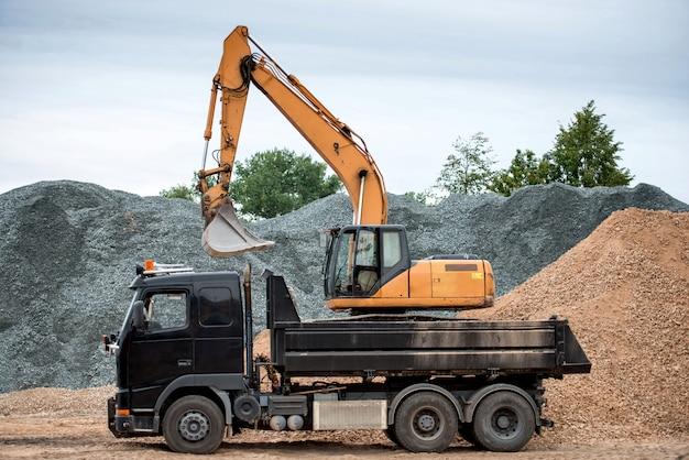 Escavatore e camion si trova nel cantiere presso la pila di ghiaia