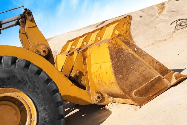 Escavatore giallo sul cantiere di nuova costruzione, con il sole splendente e bel cielo blu sullo sfondo