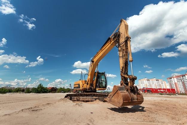 Escavatore in un cantiere edile contro un cielo blu