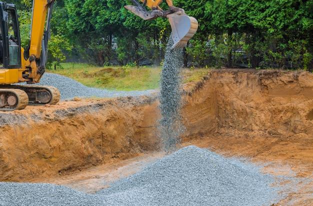 Escavatore industriale per cantiere di costruzione di fondamenta, benna, ghiaia