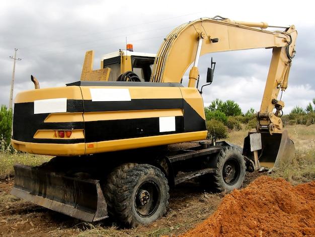 Escavatore parcheggiato sul campo con cielo coperto.