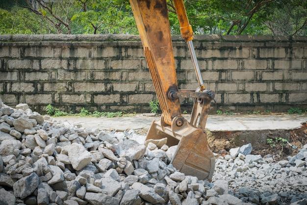 Escavatore pesante dell'organo con la pala che sta sulla collina con le rocce