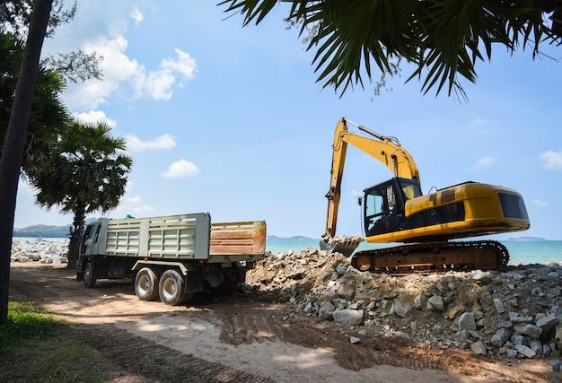 Escavatore pietra scavatrice e autocarro con cassone ribaltabile che lavora in cantiere