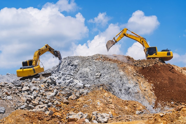 Escavatori e macchina per la frantumazione di pietre sotto un cielo blu con nuvole