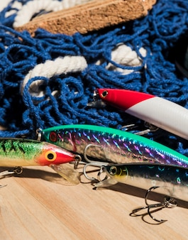 Esche da pesca colorate con rete sullo scrittorio di legno