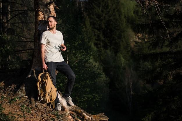 Escursione del ritratto dell'uomo con lo zaino che cammina in natura. sorridere caucasico dell'uomo soddisfatto della foresta nella priorità bassa durante il viaggio di estate