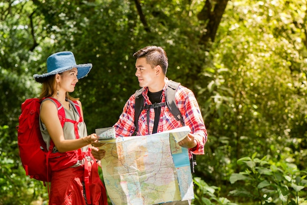 Escursioni - escursionisti che guardano la mappa. coppia, amici, navigare, insieme, sorridente, felice, campeggio, camminare, escursione, fuori, foresta. giovane razza mista razza asiatica donna e uomo.